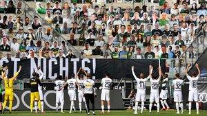 Los jugadores del Borussia de Mönchengladbach se dirigen a las gradas del estadio, ocupadas con fotografías de sus aficionados.