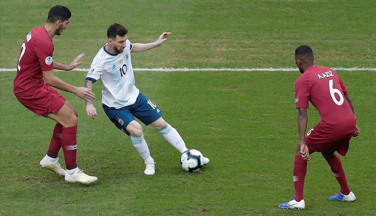Messi controla un balón, vigilado por jugadores de Qatar.