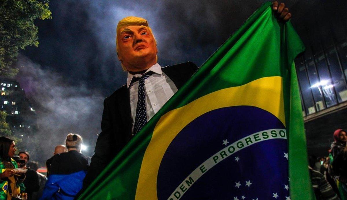 Un simpatizante de Bolsonaro luce una máscara de Trump durante las celebraciones por la victoria del dirigente brasileño en Sao Paulo.