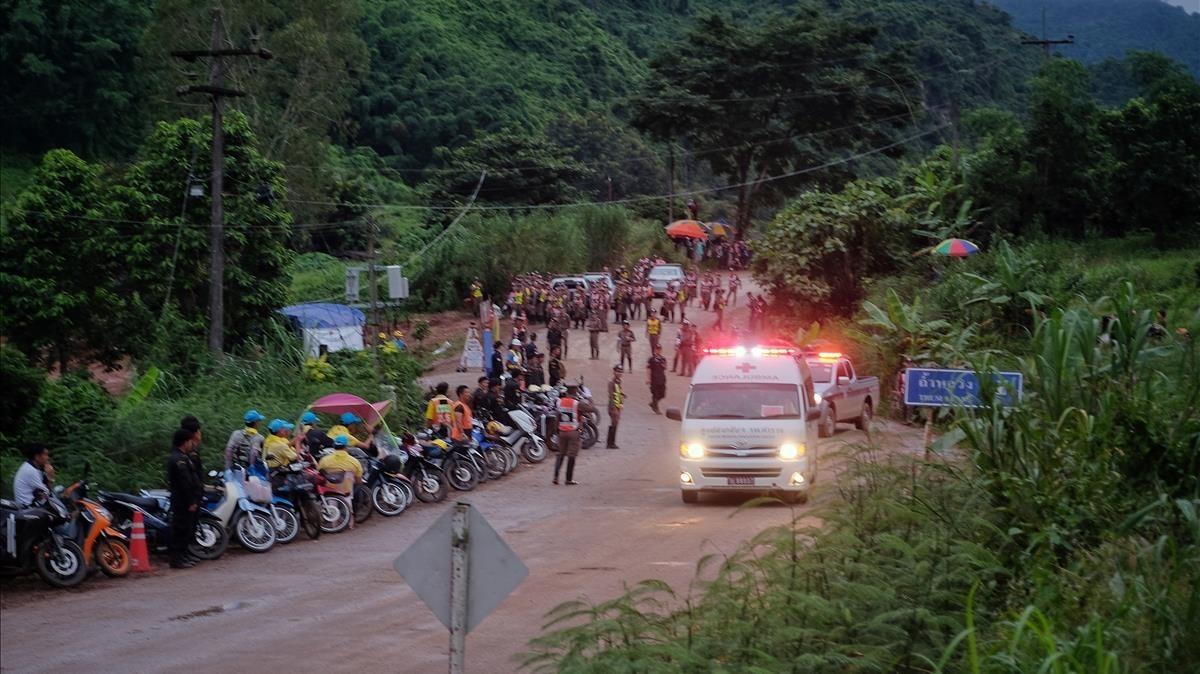 Una ambulancia con uno de los niños rescatados pasa entre una multitud de gente.