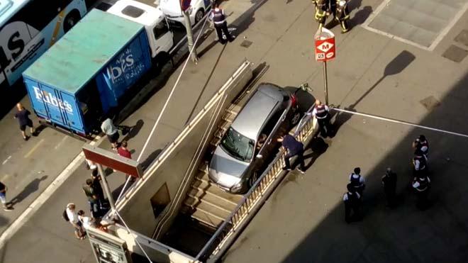 Una conductora encasta su coche en una boca del metro de la plaza Espanya de Barcelona.