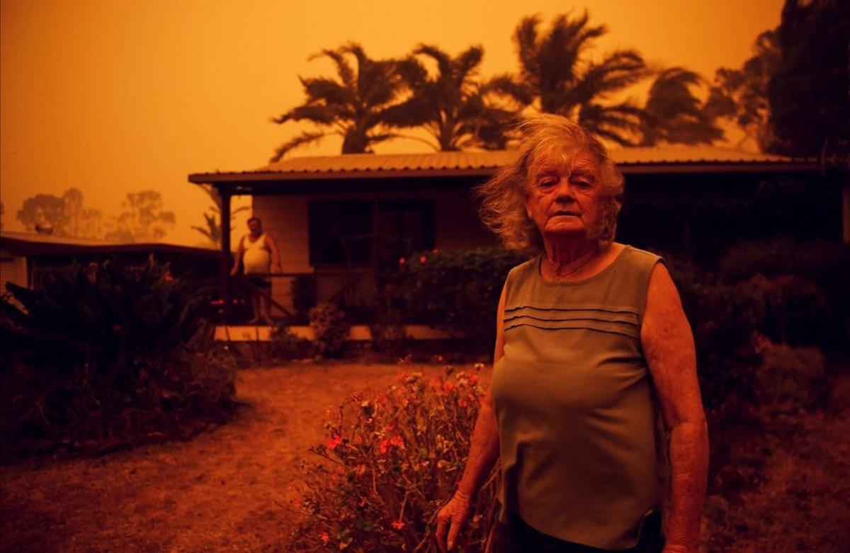 Una mujer mira a la cámara frente a su casa, azotada por los fuertes vientos que empujan el humo de los incendios en Nueva Gales del Sur, Australia