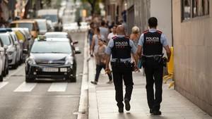 Una pareja de Mossos patrulla por una calle de Barcelona.