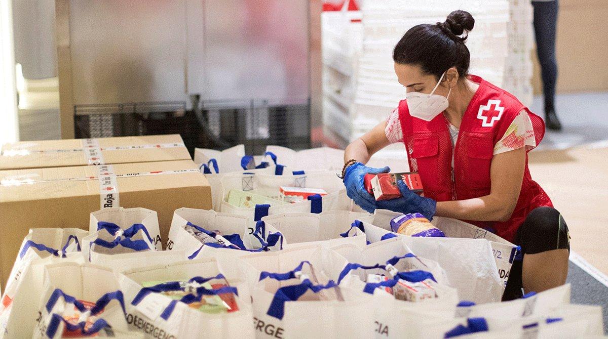 Una voluntaria prepara paquetes de alimentación básica en el almacén de la Cruz Roja en Barcelona, el 6 de mayo.