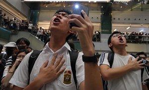 Unos jóvenes entonan el himno 'Gloria a Hong Kong' en un centro comercial.