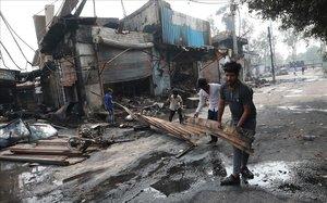 Varios hombres sacan material quemado de un edificio afectado por las protestas entre hindús y musulmanes en Nueva Deli, este miércoles.