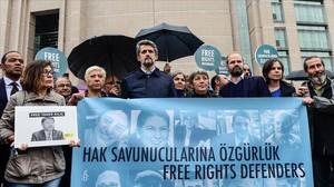 Un grupo de manifestantes protestan contra el juicio a los activistas de derechos humanos en Estambul.