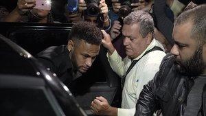 Neymar protegido a la salida de la comisaría de Sao Paulo tras ser interrogado por la policía brasileña por la acusación de violación en junio del 2019.