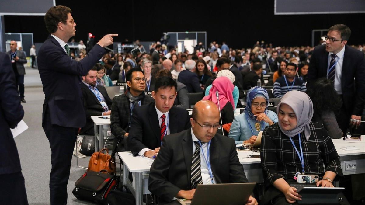 El ministro de Brasil, Ricardo Salles, charla con los miembros de sudelegación durante el plenario del viernes.