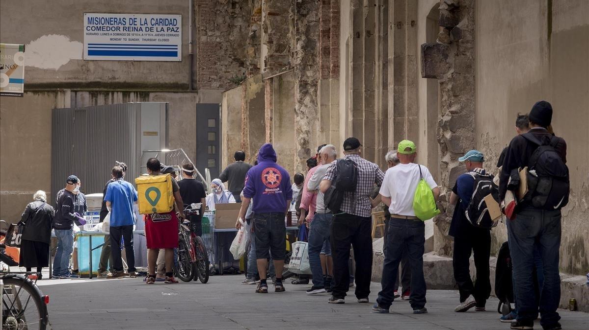 Colas para recoger comida en un comedor social del Raval de Barcelona, el pasado mayo.