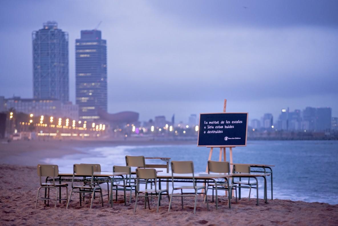 Pupitres y sillas vacías en la playa de Barcelona para denunciar que más de la mitad de las escuelas en Siria están vacías o destruidas.
