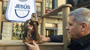 Alberto Fernández Díaz coloca una figura en el pesebre instalado en la plaza Sant Jaume