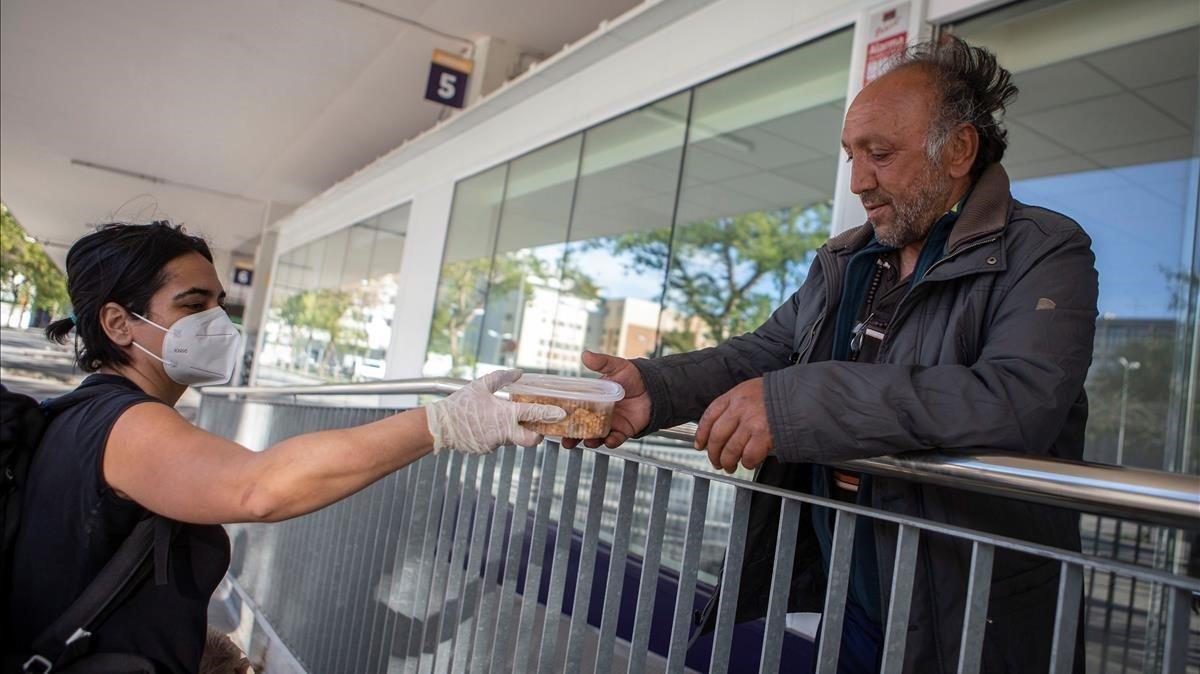 El indigente que se hace llamar Hristo Stoickov recibe la ayuda de una voluntaria de la Fundació Arrels, en Barcelona.