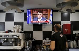 Un camarero sigue la declaración de Tsipras a través de la televisión, este miércoles en Atenas (Grecia).