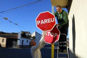El momento en que se cambia la señal de 'Stop' por la de 'Pareu' en el municipio de Torrelameu. En la foto, el alcalde, Carles Comes, y un operario municipal.