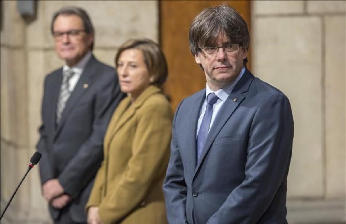 Carles Puigdemont, junto a Carme Forcadell y Artur Mas, en la toma de posesión de los consellers del Govern.