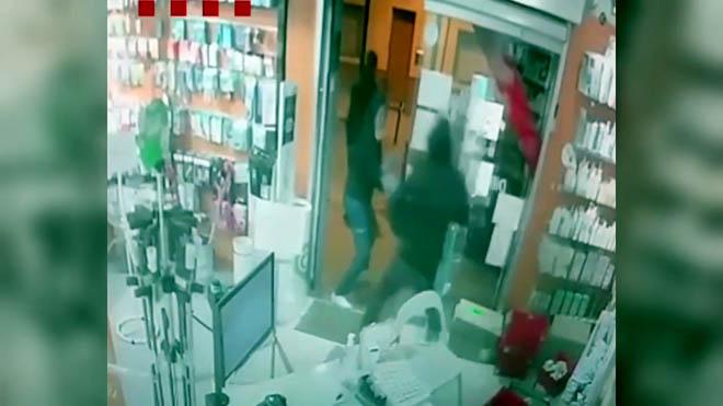 Momento en que el ladrón empuja a la empleada de la farmacia para acceder al local y robar la caja registradora.