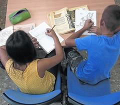 Dos niños hacen deberes.