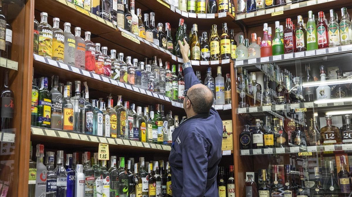 Estanteríascon botellas alcohólicas en un colmado de a calle Ferran.