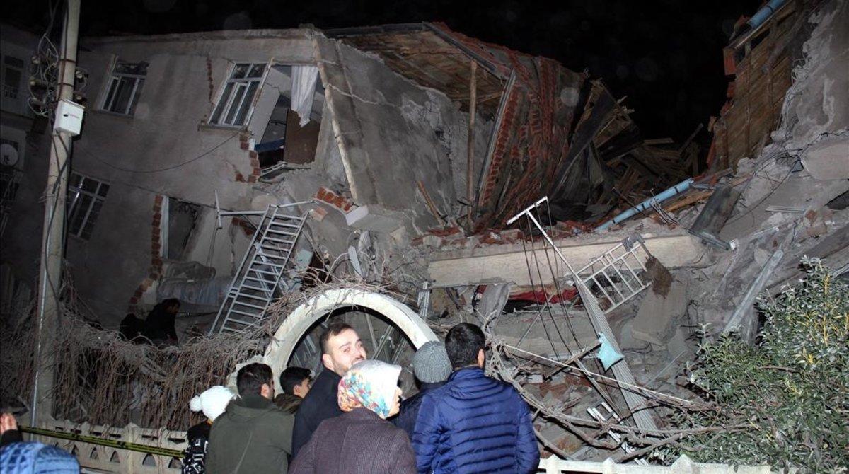 Un grupo de personas mira cómo ha quedado une dificio tras el terremoto.