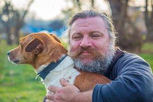 Un hombre con barba junto a su perro.