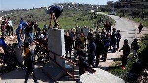 Jóvenes palestinos retiran una barrera de la entrada del pueblo de Aboud, en la Cisjordania ocupada por Israel.