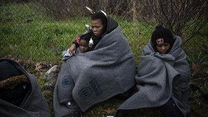 Dos refugidas con sus hijas de protegen del frío con unas mantas de ACNUR en la isla griega de Lesbos.