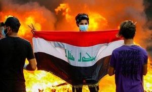Un manifestante sostiene la bandera iraquí durante unas protestas contra el Gobierno del país, en Bagdad.