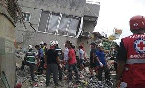 Miembros del servicio de rescate inspeccionan un edificio en Padada Davao afectado por el terremoto en busca de víctimas.