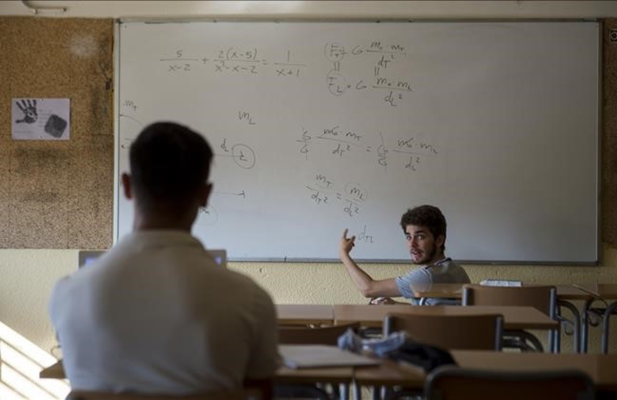 Un monitor charla con un estudiante de secundaria en una clasede refuerzo estival en el instituto Sant Andreu de Barcelona.