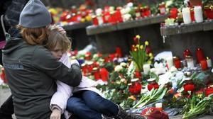 Un mujer reconforta a un niño junto a las velas y flores dejadas en la escuela Albertville, tras el tiroteo, en Winnenden (Alemania), el 12 de marzo del 2009.