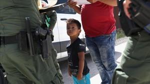 Un niño y sus padres, procedentes de Honduras, son retenidos por una patrullapolicialcerca de la frontera de EEUU con México en Misión (Tejas), el 12 de junio pasado.