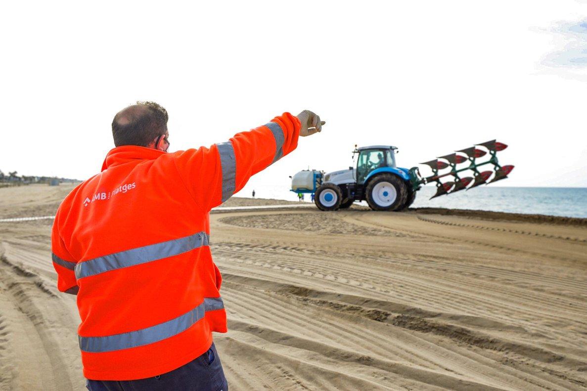 Un operario y un tractor labrando la playa de Castelldefels, este martes