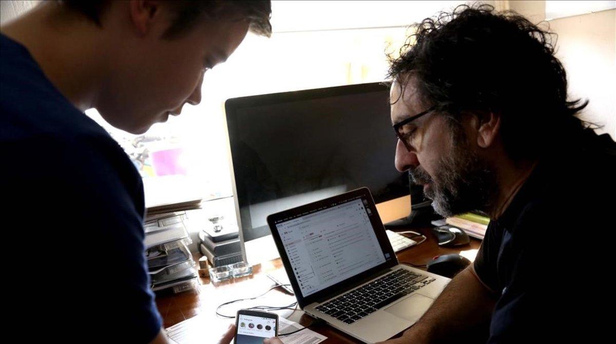 Un padre y su hijo navegan por las redes sociales, en su casa de Madrid.