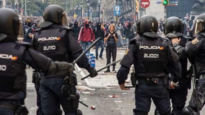 Un policía nacional graba los disturbiosdesde la furgonetaen Barcelona.