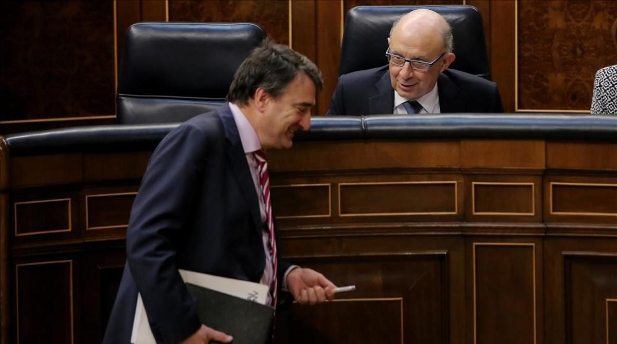 El portavoz del PNV, Aitor Esteban, bromea con el ministro de Hacienda, Cristóbal Montoro, este miércoles en el Congreso.