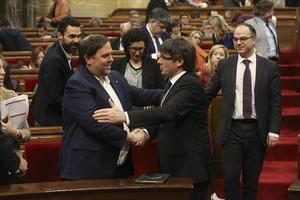 Puigdemont y Junqueras se felicitan durante el pleno.