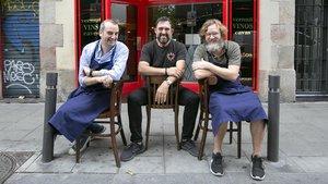 Sentados en la calle ante la puerta del Bar Leopoldo: Romain Fornell, Òscar Manresa y Rafa Peña.