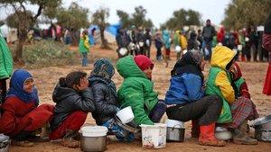 Niños sirios hacen cola para recibir comida en un campo de desplazados cerca de la localidad deYazi Bagh, cerca de la frontera entre Siria y Turquía.
