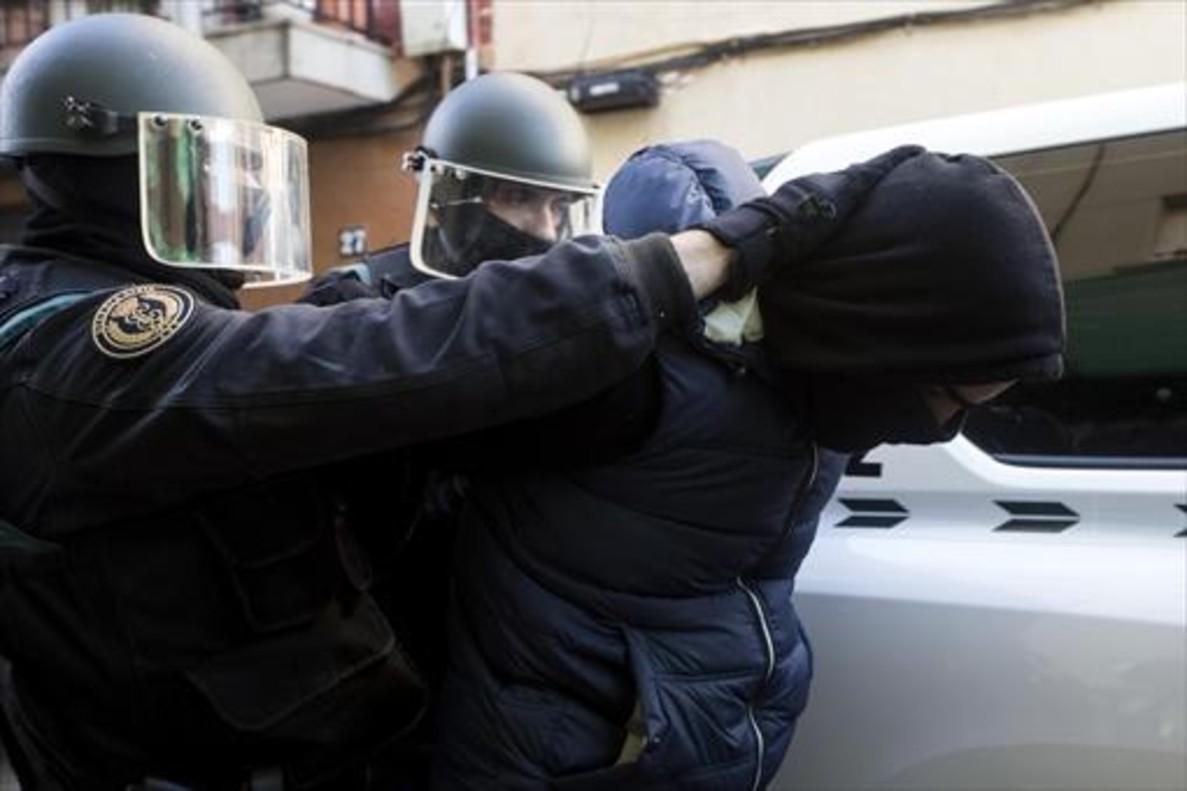 Traslado de uno de los dos detenidos, este martes, 7 de febrero, en Badalona, bajo la acusación de captar y adoctrinar a yihadistas.