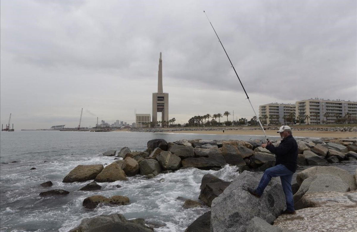 Un hombre pesca con las Tres Chimeneas de Sant Adrià al fondo.