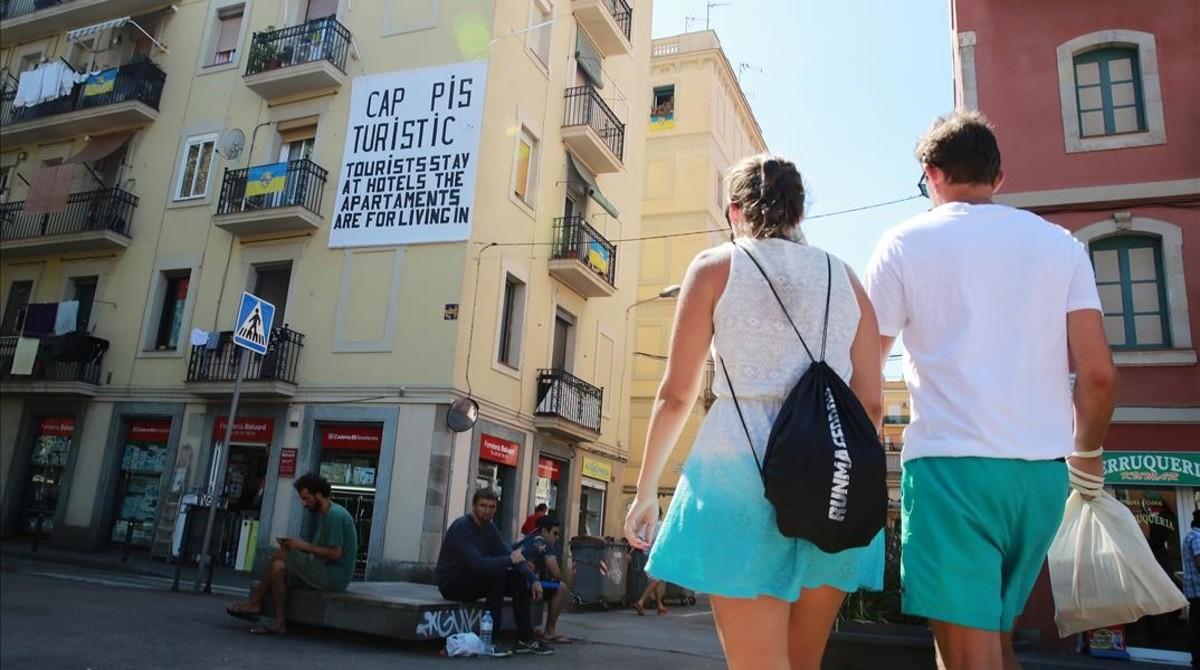 Una pareja pasea por el barrio de la Barceloneta.