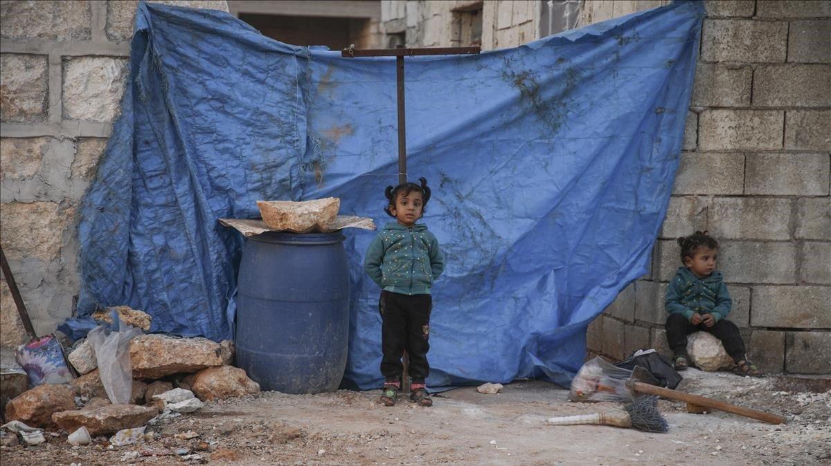 Unas niñas sirias, ante una de las estancias donde permanecen los desplazados, en Alepo.