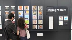 Varias personas contemplan las fotografías expuestas en el Movistar Centre de Barcelona.