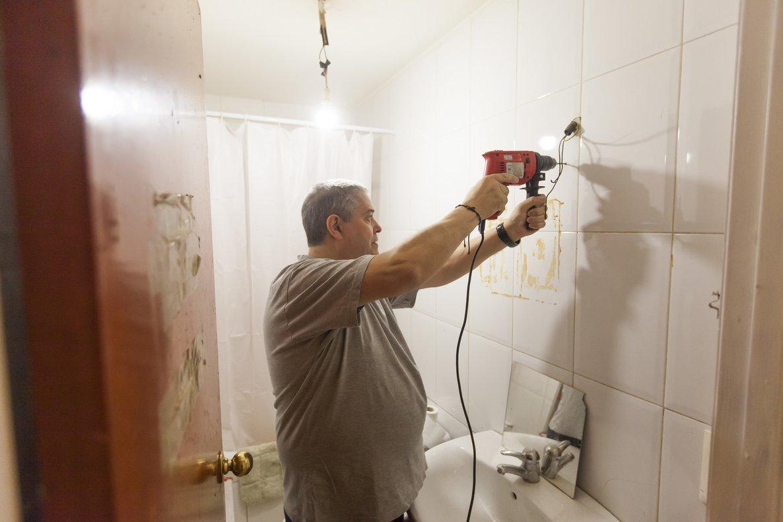 El voluntario Alfonso Fernández hace los agujeros para poner un espejo en el baño de los Amaya.