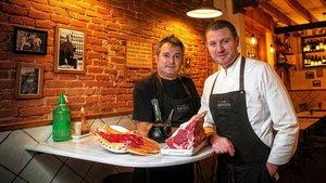 Josep Barragán y el cocinero Txema Martínez ante un porrón y algunas viandas en la Bodega Amposta.