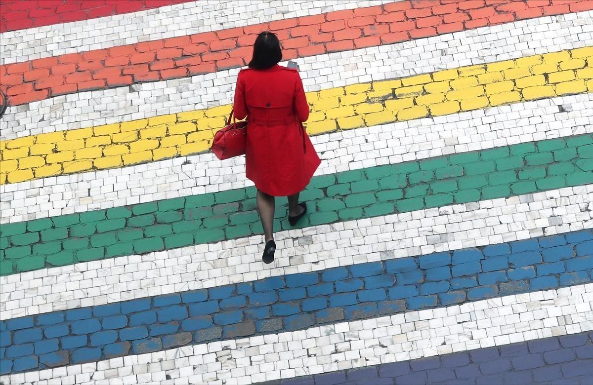 Una mujer cruza una carretera cerca del Parlamento de la UE en Bruselas, Bélgica.