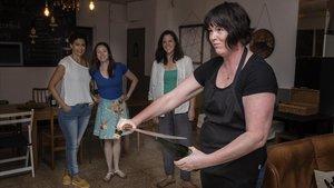 La sumiller espadachina Zara Patterson descorcha una botella de un machetazo delante de tres alumnas en Uncorked Academy.