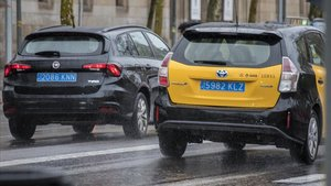 Un taxi y un VTC, los dos identificados con matrícula azul, circulando juntos por Barcelona, el viernes.