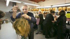 Burget Tapias, en el almacén de la tienda, dando un toque natural a una peluca lista para ser lucida.